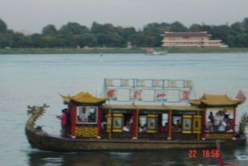 Pleasure boat with dragon head on the bow on the Yalu River, North Korea in the background