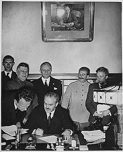 Molotov  signing the Nazi-Soviet Pact - to his right Stalin and next Ribbentrop